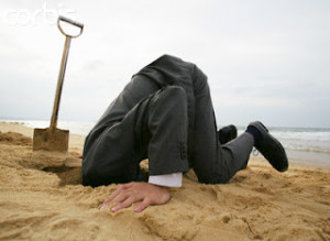 Businessman With Head in Sand --- Image by © cocorophotos/Bloomimage/Corbis