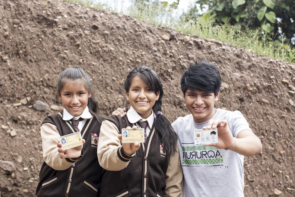 Juan y sus hermanas muestran orgullosos sus identificaciones. © Daniel Silva Yoshisato/Banco Mundial